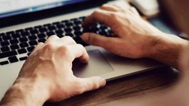 Händer som skriver på bärbar dator